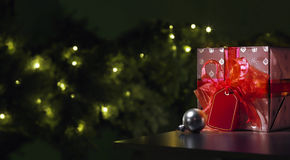 Presente vermelho do Natal com uma árvore no fundo Fotografia de Stock