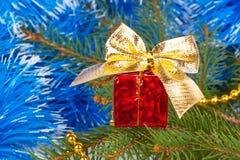 Presente vermelho do Natal com uma curva sob a árvore de Natal Imagens de Stock
