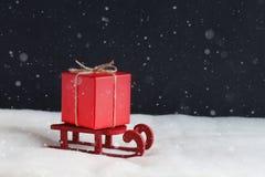 Presente vermelho no pequeno trenó de madeira na neve Imagem de Stock