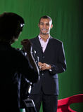 Presenter and camera operator. Presenter in a green screen Television studio chats with a camera operator silhouetted in foreground Royalty Free Stock Photo