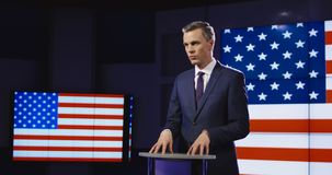 Presenter in front of American flag. Public speaker or presenter in front of American flag standing at a small rostrum speaking and gesturing emphatically with stock video