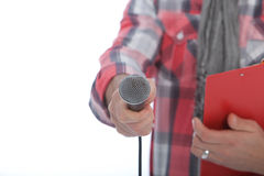 Presenter or interviewer holding out a microphone Royalty Free Stock Photography
