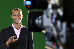 Presenter in TV Studio with foreground camera Royalty Free Stock Photo
