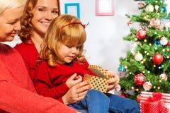 Presentes abiertos de la niña con la madre y la abuelita Fotos de archivo libres de regalías