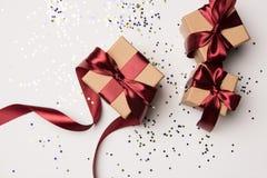 Presentes arranjados com fitas vermelhas e confetes isolados no branco Imagem de Stock