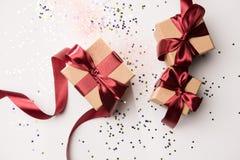 Presentes arranjados com fitas vermelhas e confetes isolados no branco Fotografia de Stock Royalty Free