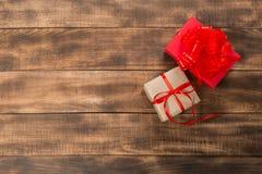 Presentes com a fita vermelha na tabela de madeira fotografia de stock royalty free