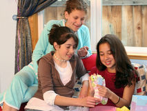 Presentes da abertura da menina em sua festa de anos Fotografia de Stock Royalty Free