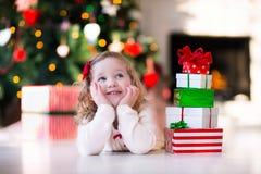 Presentes da abertura da menina na manhã de Natal Imagens de Stock
