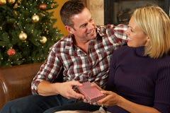 Presentes da abertura dos pares na frente da árvore de Natal Fotografia de Stock Royalty Free