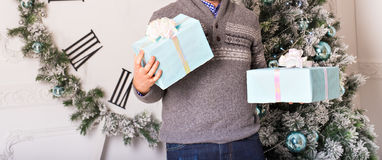Presentes da terra arrendada do homem novo na frente da árvore de Natal Imagem de Stock
