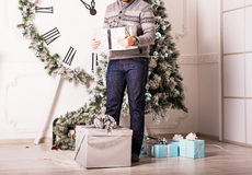 Presentes da terra arrendada do homem novo na frente da árvore de Natal Imagens de Stock