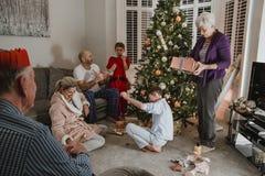 Presentes de apertura el mañana de la Navidad Imágenes de archivo libres de regalías