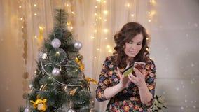 Presentes de compra da menina emocional bonito nova com cartão de crédito e smartphone no Natal perto da árvore de Natal vídeos de arquivo