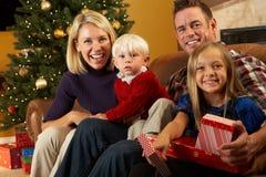 Presentes de la apertura de la familia delante del árbol de navidad Foto de archivo libre de regalías