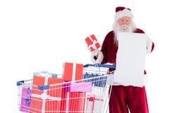 Presentes de la extensión de Papá Noel con el carro de la compra fotografía de archivo libre de regalías