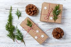 Presentes de la Navidad o del Año Nuevo envueltos en papel coloreado natural y adornados con las ramitas tradicionales de la guit Imagen de archivo