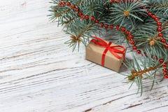 Presentes de la Navidad o del Año Nuevo envueltos en papel coloreado natural y adornados con las ramitas tradicionales de la guit Imagenes de archivo