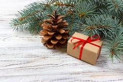 Presentes de la Navidad o del Año Nuevo envueltos en papel coloreado natural y adornados con las ramitas tradicionales de la guit Imágenes de archivo libres de regalías