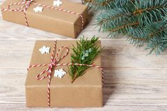 Presentes de la Navidad o del Año Nuevo envueltos en papel coloreado natural y adornados con las ramitas tradicionales de la guit Foto de archivo libre de regalías
