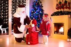 Presentes de Natal da abertura das crianças e da Santa Foto de Stock Royalty Free