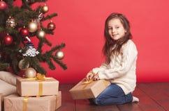 Presentes de Natal de sorriso da abertura da menina sobre o vermelho Imagens de Stock
