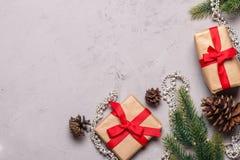 Presentes de Natal decorados com a fita vermelha no fundo de pedra cinzento Foto de Stock