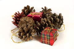 Presentes de Natal e cones da árvore, no branco Imagens de Stock Royalty Free