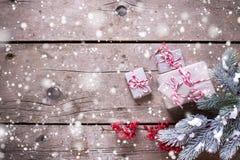 Presentes de Natal envolvidos, ramos de árvore da pele, bagas vermelhas em vi Foto de Stock