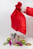 Presentes de Natal no saco vermelho que guarda o braço Fotos de Stock