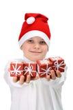 Presentes de Natal pequenos da terra arrendada do menino fotografia de stock