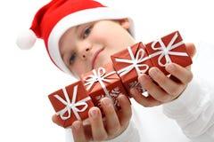 Presentes de Natal pequenos da terra arrendada do menino isolados imagem de stock