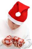 Presentes de Natal pequenos da terra arrendada do menino isolados imagens de stock royalty free