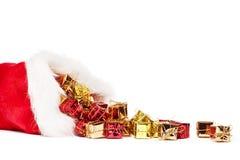 Presentes de Natal pequenos que caem do chapéu de Santa Fotografia de Stock