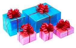 Presentes de un rosa y de las azules turquesas atados con los arcos rojos Fotografía de archivo libre de regalías