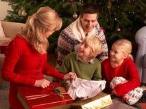 Presentes do Natal da abertura da família em casa Imagens de Stock
