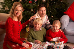 Presentes do Natal da abertura da família em casa Imagem de Stock Royalty Free