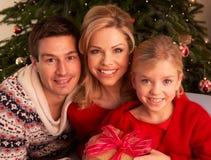 Presentes do Natal da abertura da família em casa Imagem de Stock