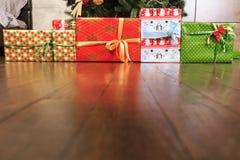 Presentes do Natal e do ano novo sob a árvore no assoalho de madeira Fotos de Stock Royalty Free