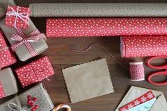 Presentes do Natal e papel de embalagem em uma tabela de madeira Foto de Stock