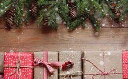 Presentes do Natal e ramos do abeto com cones em uma tabela de madeira Fotos de Stock