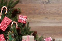 Presentes do Natal e ramos do abeto em uma tabela de madeira Fotos de Stock