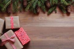 Presentes do Natal e ramos de árvore do ajuste com os cones na superfície de madeira Foto de Stock Royalty Free
