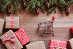 Presentes do Natal e ramos de árvore do ajuste com os cones na superfície de madeira Imagens de Stock Royalty Free