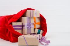 Presentes do Natal em um saco e em uma decoração no pescoço Fotografia de Stock Royalty Free