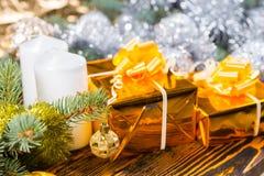 Presentes dourados festivos na tabela com decorações Foto de Stock