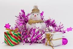Presentes e boneco de neve do Natal na fita cor-de-rosa brilhante no fundo branco Fotografia de Stock Royalty Free