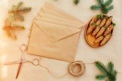 Presentes e letras feitos a mão, e tudo do Natal necessária para eles Envelopes do papel de embalagem, das tesouras, de cones spr Fotografia de Stock
