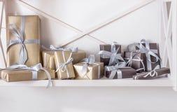 Presentes elegantes, cajas de regalo en los estantes blancos en el fondo de la pared Foto de archivo