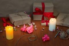 Presentes en el papel de Kraft con las cintas rojas Imágenes de archivo libres de regalías